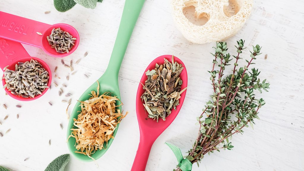 A close up of dried herbs and flower petals in measuring spoons