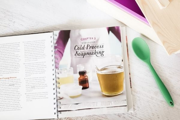 Cold process soap making book open to recipe, with soap mold and spoon